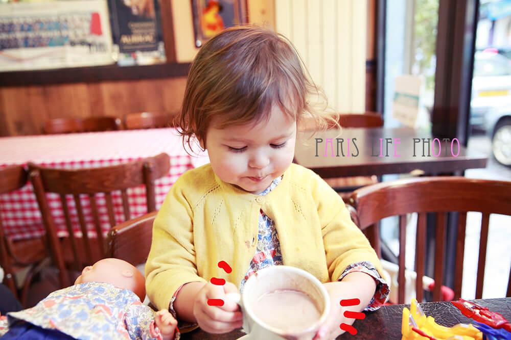 パリのカフェでカフェオレを飲む女の子