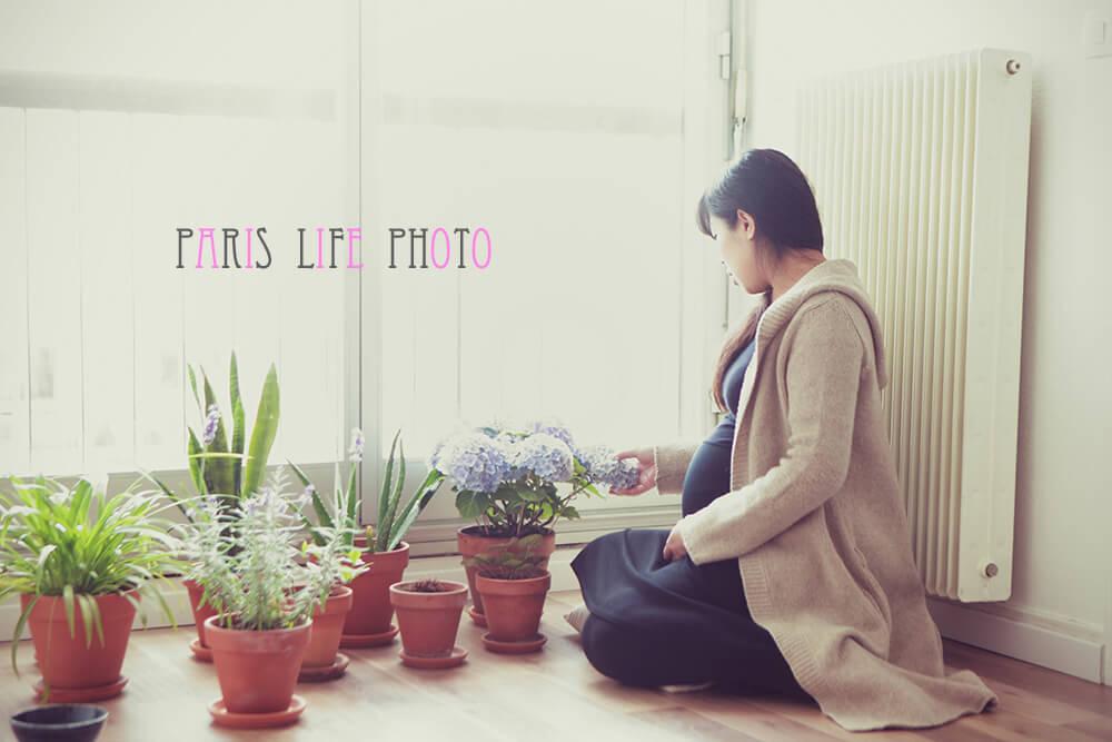 パリの自宅の窓辺で花を愛でる妊婦