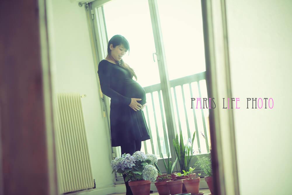 パリの自宅の窓辺でお腹に手を当てる妊婦