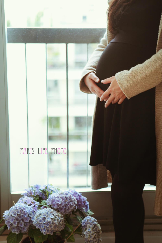 パリの自宅の窓辺でお腹に手を当てる妊婦と足もとのアジサイ
