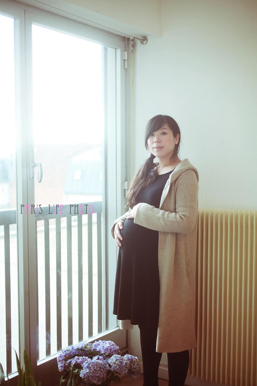 パリの自宅の窓辺でお腹に手をあてる妊婦