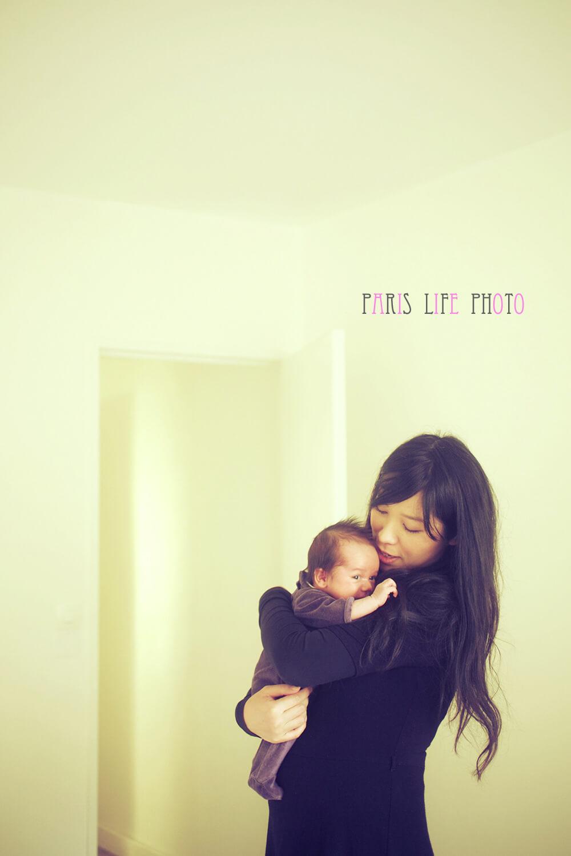 パリの自宅の窓辺で赤ちゃんを抱っこするママ