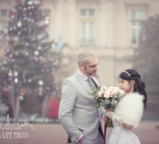 フランス、パリで挙式した新郎新婦のクリスマスツリー前でのポージング
